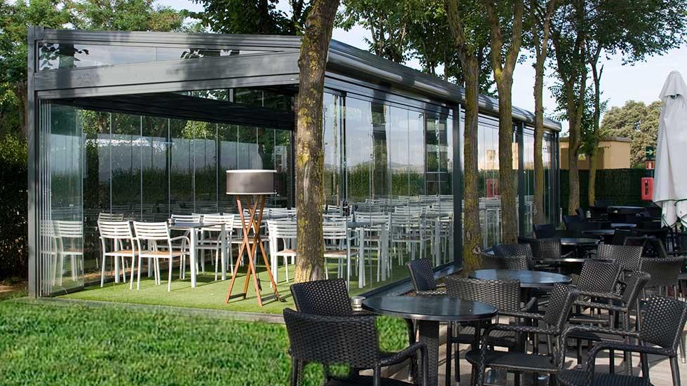 Terraza con cortinas de cristal y techo movil en la naturaleza